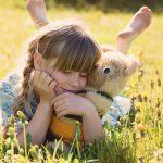 meisje knuffelt met beer in het gras